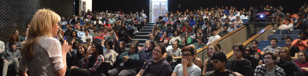 Students in an auditorium listening to Katie Koestner